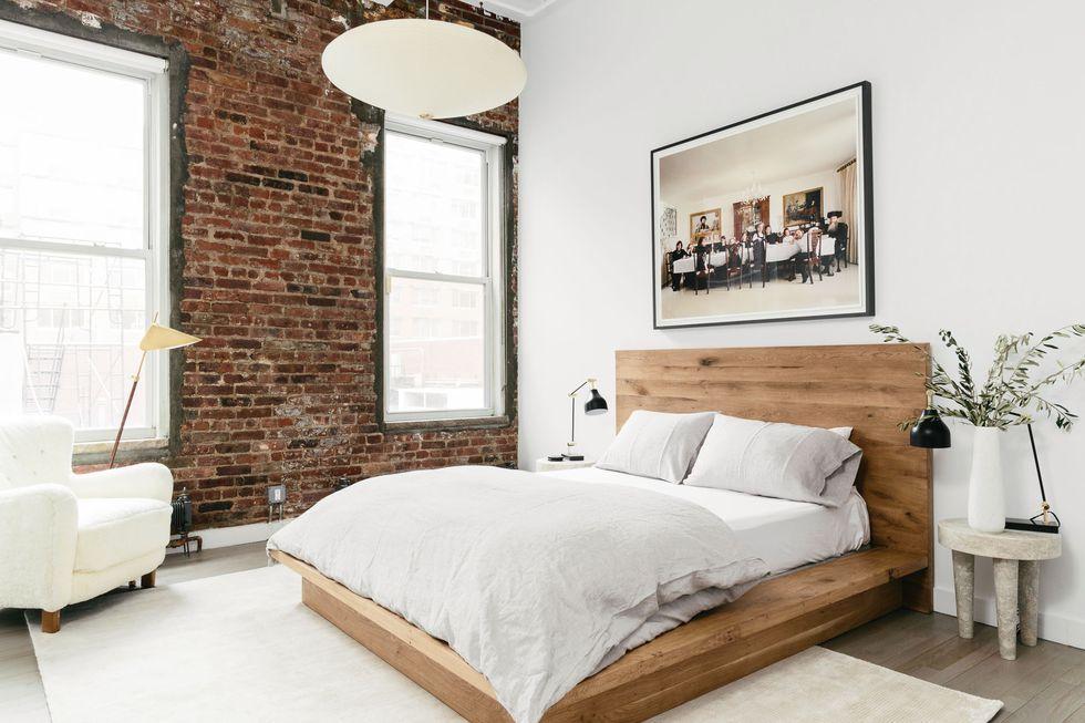 Chiếc giường từ gỗ tự nhiên kết hợp với tường gạch tạo vẻ mộc mạc, thân thiện cho căn phòng